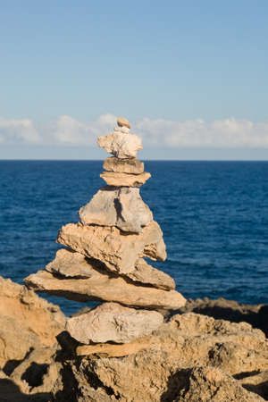 Pyramid shaped stack of rocks balanced on the edge of ocean Zdjęcie Seryjne