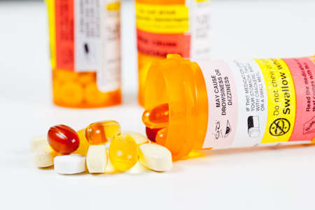 prescription drugs: Colorful vitamins spilling from prescription bottle with warnings Stock Photo