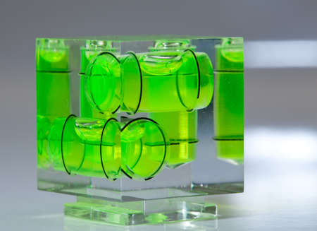 leveler: Three green spirit levels in plastic cube setting angle in any direction Stock Photo