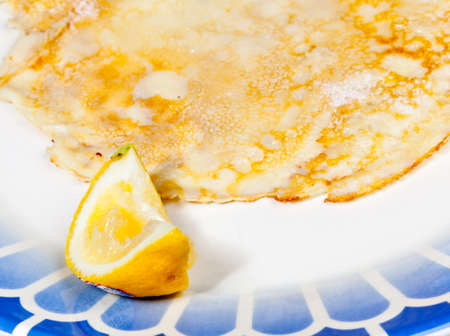 shrove tuesday: Cooked homemade pancake and lemon on blue plate