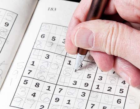 sudoku: Male hand holding pen or pencil on suduko puzzle
