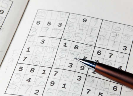 sudoku: Pencil or pen resting on completed sudoku puzzle in book