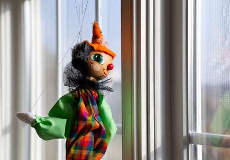 marioneta de madera: Títere o marioneta que cuelga en la ventana y mirando hacia fuera iluminada por el sol exterior