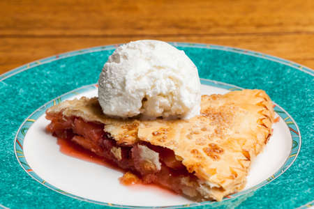 Home made baked fruit pie on plate in single serving with ice cream photo