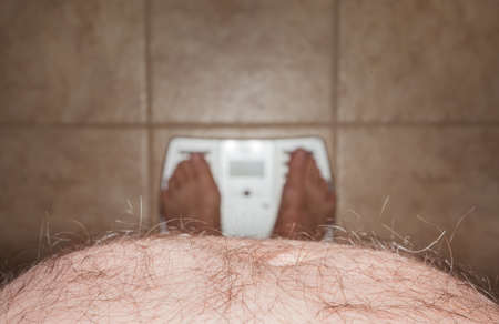 Close up of stomach of large hairy man standing on bathroom scales
