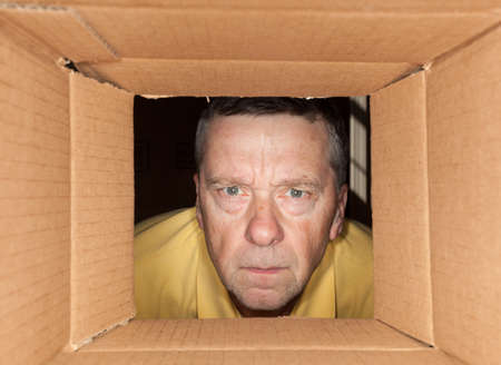 Senior caucasian man looking directly into a cardboard box and being worried Stock Photo - 12783811
