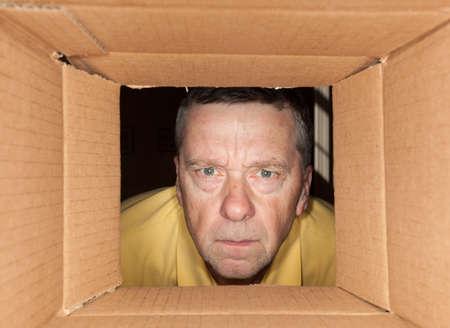 Starszy kaukaski mężczyzna szuka bezpośrednio do kartonowego pudełka i jest zmartwiony