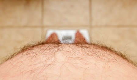 Close up of stomach of large hairy man standing on bathroom scales photo