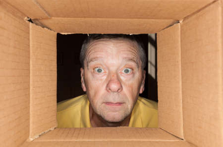 Senior caucasian man looking directly into a cardboard box and being worried Stock Photo - 12783809