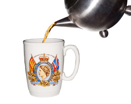 queen elizabeth: Old coronation cup  from crowning of Queen Elizabeth with tea being poured from teapot Stock Photo