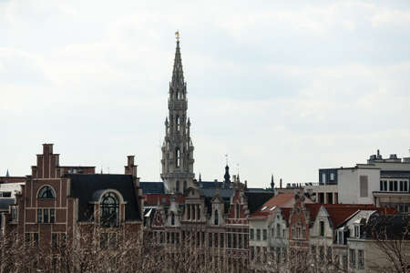 Ornate Brussels Town Hall in Grand Place over old and new buildings 免版税图像