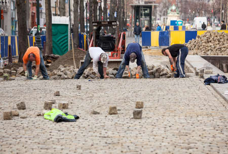 sq: BRUSSELS, BELGIUM - MARCH 19: Workers laying cobblestone road in Brussels on March 19, 2012. City of Brussels covers 12.6 sq. miles with 146000 inhabitants