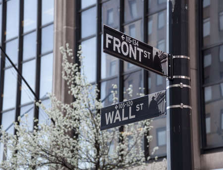 directly below: Street signs at end of Wall Street by Front Street in New York City