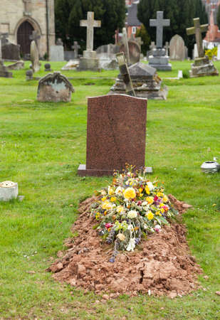 bury: Flowers on the top of a newly dug burial site in graveyard Stock Photo