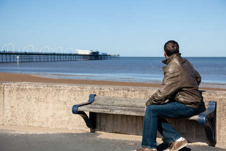 sitting on a bench: Single caucasian male looking at sea and pier in Southport England