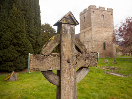 Ancient wooden cross in cemetery of old parish church of Stokesay in Shropshire photo