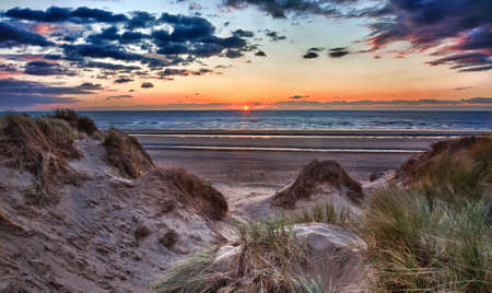 Sun setting over the beach at Formby in England through sand dunes Stock Photo