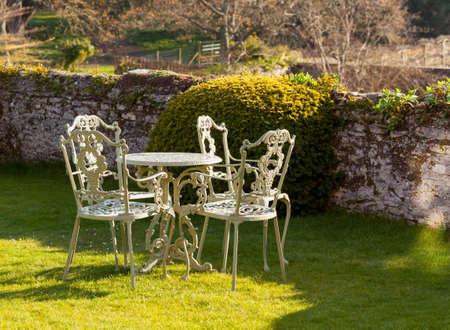 돌 벽에 의해 잔디밭에 철 정원 테이블과 의자 캐스트