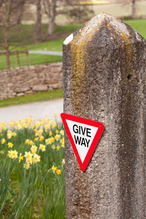 countrysides: Modern give way sign on rural road fixed to old stone post