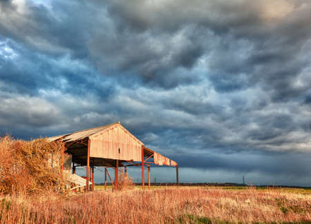evenings: Storm clouds over sunlit deserted and ruined barn on farmland Stock Photo