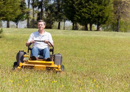 Senior retired male cutting the grass on expansive lawn using yellow zero-turn mower Stock Photo - 13295098