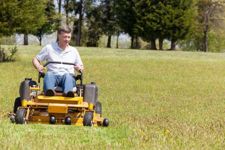 노란색 제로 턴 모어를 사용하여 넓은 잔디밭에 잔디를 절단 수석 은퇴 한 남성