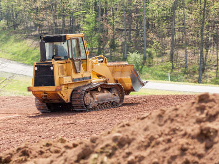 earth moving: Land being levelled and cleared by yellow earth moving digger