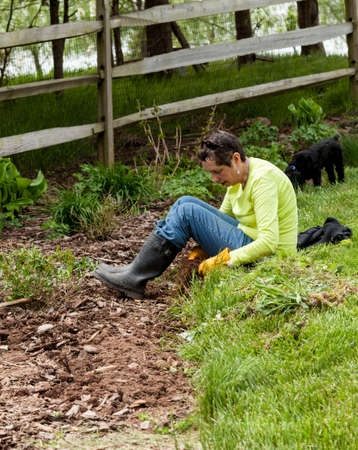 Woman gardener sits on grass when weeding flowerbed Stock Photo - 13295110