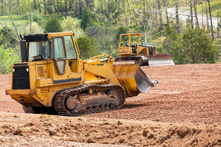 industrial machinery: Land being levelled and cleared by yellow earth moving digger