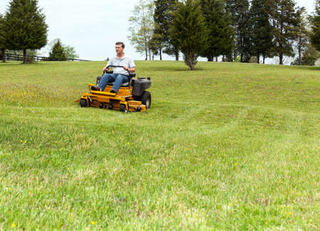 lawn mowing: Senior retired male cutting the grass on expansive lawn using yellow zero-turn mower