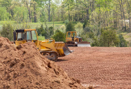 earthmover: Land being levelled and cleared by yellow earth moving digger