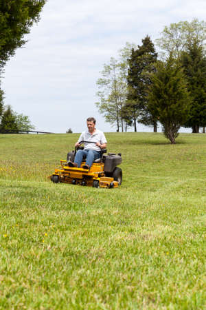 mow: Senior retired male cutting the grass on expansive lawn using yellow zero-turn mower