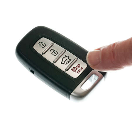 Finger pressing alarm on black modern car door opener and keyless entry device photo