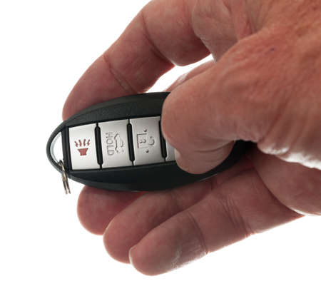 key fob: Black modern car door opener and keyless entry device with thumb pressing lock