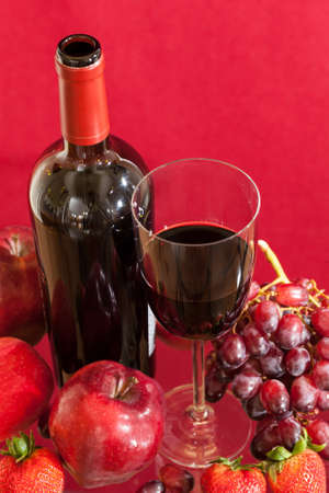 Red wine bottle and red wine in glass with red apples, grapes and strawberries photo