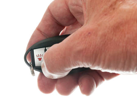 Black modern car door opener and keyless entry device with thumb pressing alarm photo