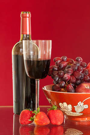 Red wine bottle and red wine in glass with red apples, grapes and strawberries