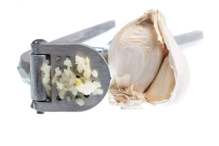 Garlic press and garlic isolated against white in macro shot