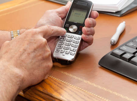 phone button: Caucasian man pressing buttons on wireless phone on leather desk
