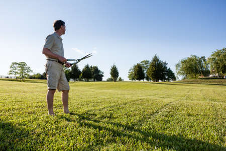 Challenging task of cutting large lawn with grass shears by hand photo