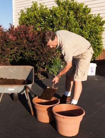 Senior male turning over dirt in wheelbarrow Stock Photo - 13608314