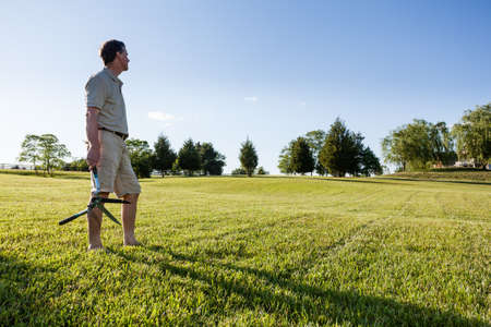 Challenging task of cutting large lawn with grass shears by hand Stock Photo - 13608330