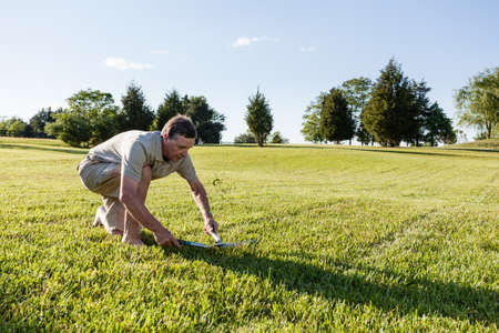 resilience: Challenging task of cutting large lawn with grass shears by hand Stock Photo