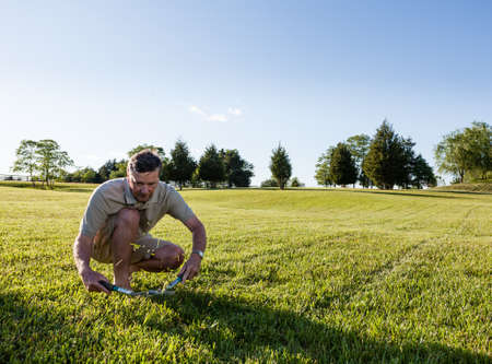 succeeding: Challenging task of cutting large lawn with grass shears by hand Stock Photo