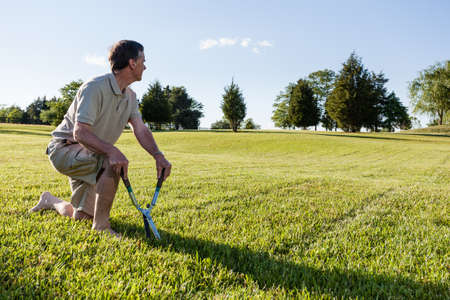 challenged: Challenging task of cutting large lawn with grass shears by hand Stock Photo