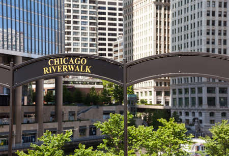 Brown arched sign to Chicago Riverwalk with tribune tower in background photo