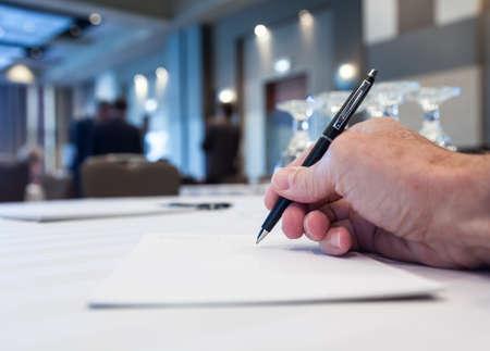 hombre escribiendo: Conferencia de mesa con la mano tomando notas o minutos con la gente en el fondo Foto de archivo