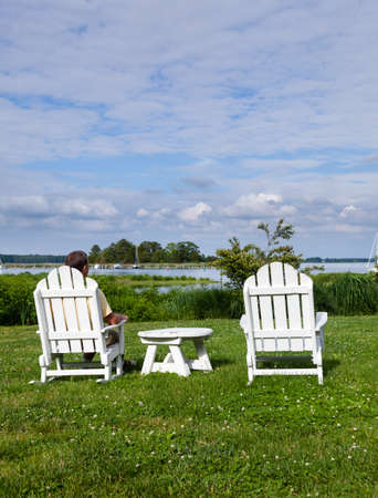 Patio chairs by side of the Chesapeake bay overlooking St Michaels harbor with senior male photo