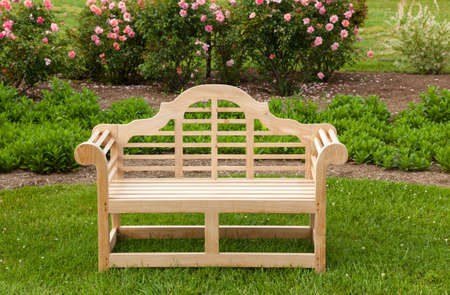 seating furniture: Teak carved bench on lawn by flower bed with rose bushes Stock Photo