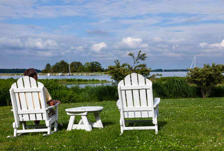 patio chairs: Patio chairs by side of the Chesapeake bay overlooking St Michaels harbor with senior male